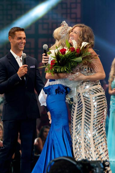 Cassidy Wolf, Miss Teen USA 2013 hugs host Miss Teen USA 2003, Tami Farrell as host Karl Schmid watches